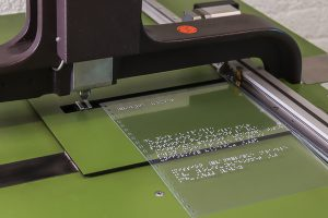 Embossing machine with the plastic cover of a book provided with braille