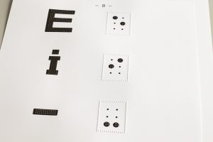 Paper with letters and corresponding braille signs printed with black ink combined with tactile dots