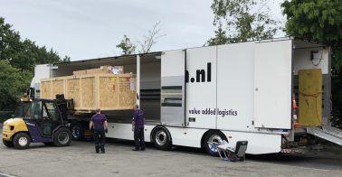 Een grote houten kist wordt met heftruck uit een vrachtwagen gehaald.
